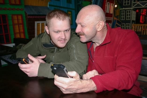 Le père et le fils communiquent assis à la table et étudient les informations sur les téléphones