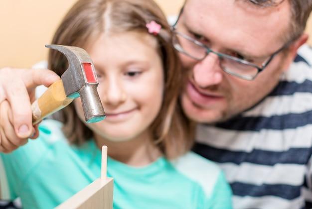 Le père et les fils construisent les meubles à la maison