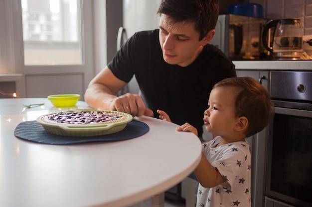 Père et fils dans la cuisine. enfant veut un délicieux gâteau chaud.