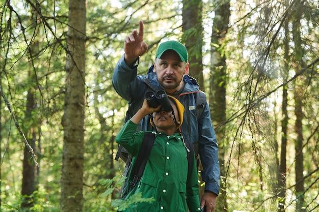 Père et fils debout dans la forêt et à l'aide de jumelles pour regarder une vue magnifique