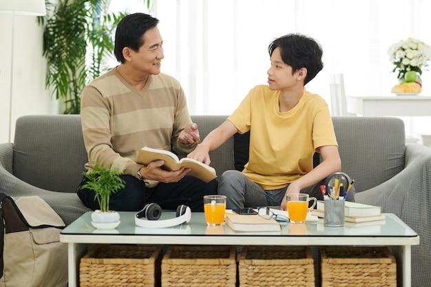 Père et fils discutant de sujets difficiles et d'exemples dans le livre des étudiants lorsqu'ils sont assis sur un canapé à la maison