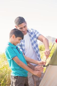 Père et fils dressant leur tente