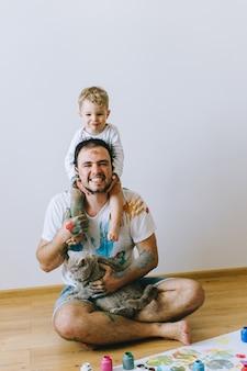 Père avec un fils sur les épaules et un chat sur les mains peint avec de la peinture