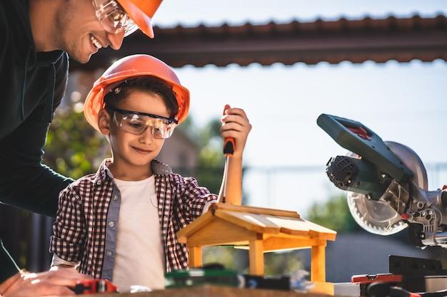 Le père et le fils fabriquent ensemble une mangeoire à oiseaux en bois
