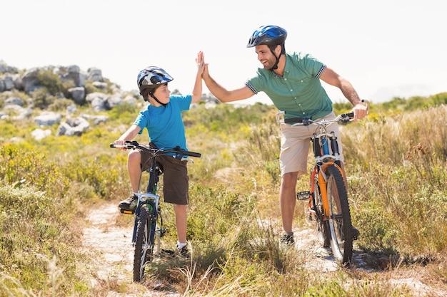 Père et fils, faire du vélo à travers les montagnes