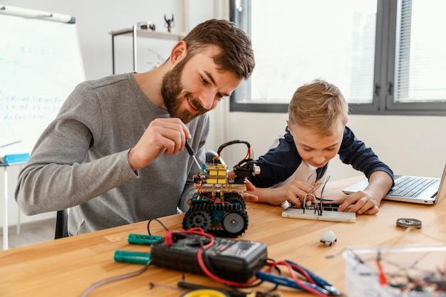 Père et fils faisant un robot