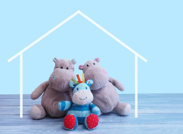 Le père et le fils de la famille du jouet hippopotame sont assis sur un plancher en bois gris