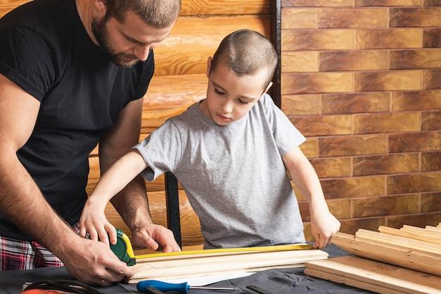 Père et fils font ensemble un nichoir en bois dans l'atelier