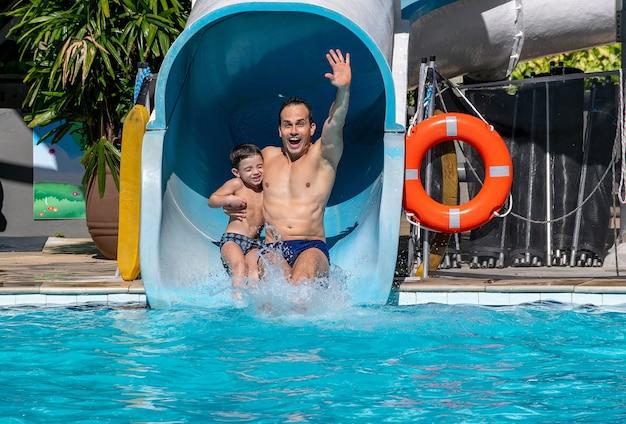 Père et fils sur une glissade d'eau ensemble