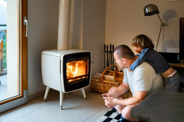 Père et fils jouant au coin du feu dans un salon. concept de parents et d'enfants. passer du temps ensemble. garçon et papa à la maison le soir.