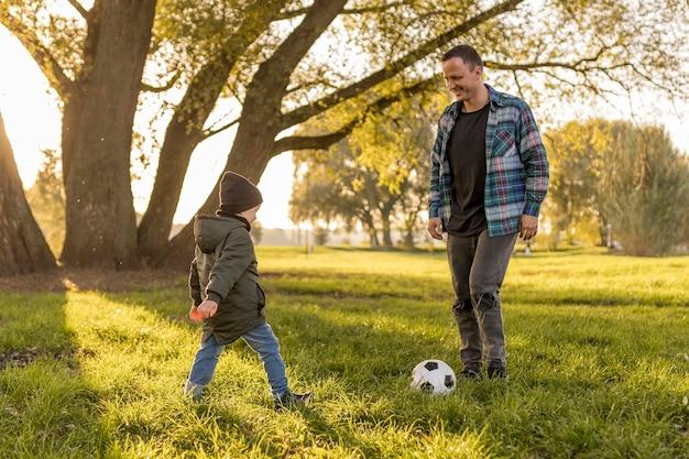 Père et fils jouant au football dans le parc