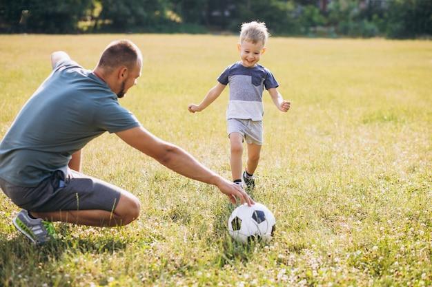 Père et fils jouant au football sur le terrain