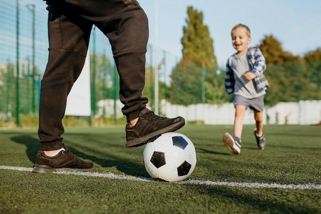 Père et fils jouant au football