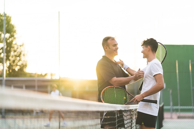 Père et fils jouant au tennis à l'extérieur
