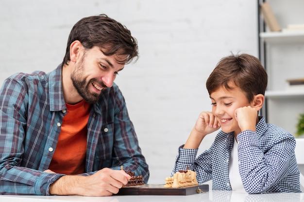 Père et fils jouant aux échecs