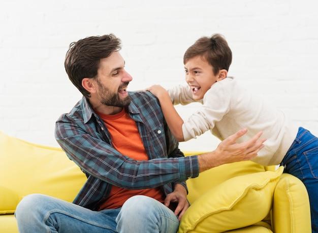 Père et fils jouant sur un canapé