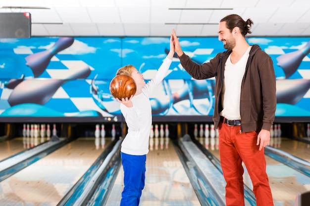 Père et fils jouant dans un centre de bowling