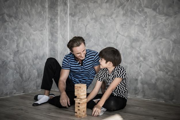 Père et fils jouant jenga dans la maison. concept de famille heureuse.