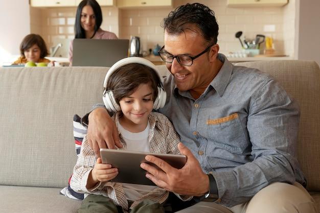 Père et fils jouant à un jeu sur une tablette