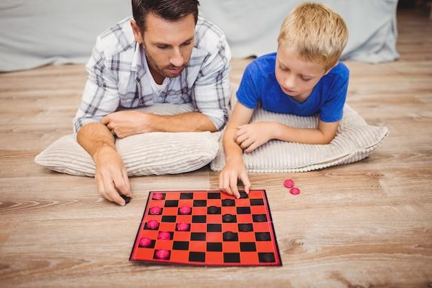 Père et fils jouent au jeu de dames en étant allongés sur le plancher