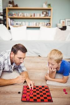 Père et fils jouent au jeu de dames à la maison