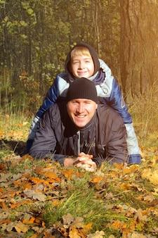 Père et fils jouent dans la forêt d'automne un adolescent d'apparence européenne rit avec son père