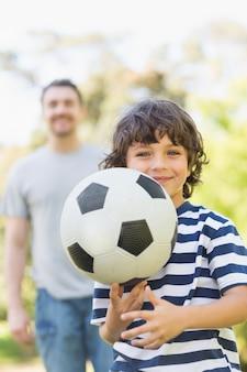 Père et fils, jouer au football dans le parc