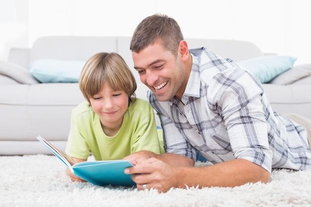 Père et fils, lecture de livre en position couchée sur le sol
