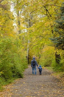 Père et fils sur leurs épaules marchent dans le parc d'automne.