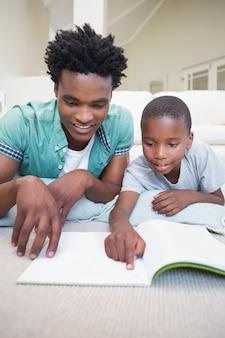 Père et fils lisant par terre