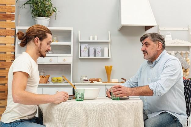 Père et fils mangent ensemble
