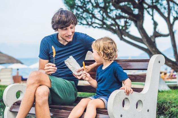 Père et fils mangent des patates douces frites dans le parc sur le banc