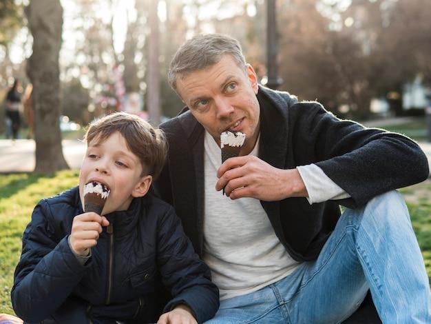 Père fils, manger glace, dans parc