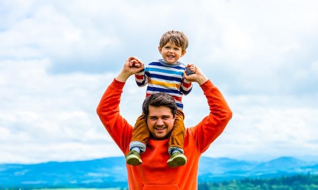 Père avec fils marchant à l'extérieur avec des montagnes derrière