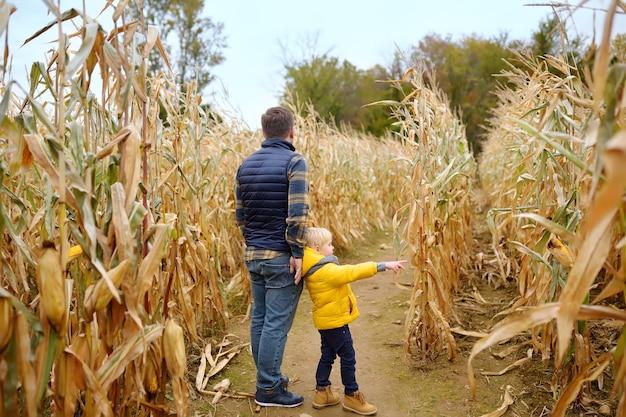Père et fils marchant parmi les tiges de maïs séchées dans un labyrinthe de maïs