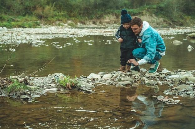 Père et fils marchent et jouent ensemble. l'automne dans les montagnes.