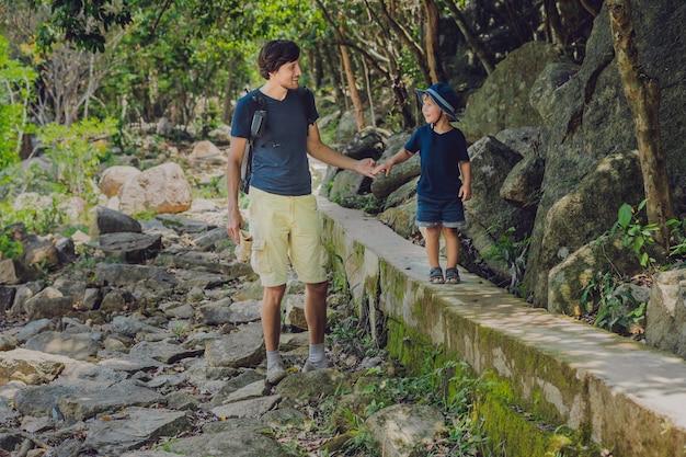Père et fils marchent le long de la route forestière