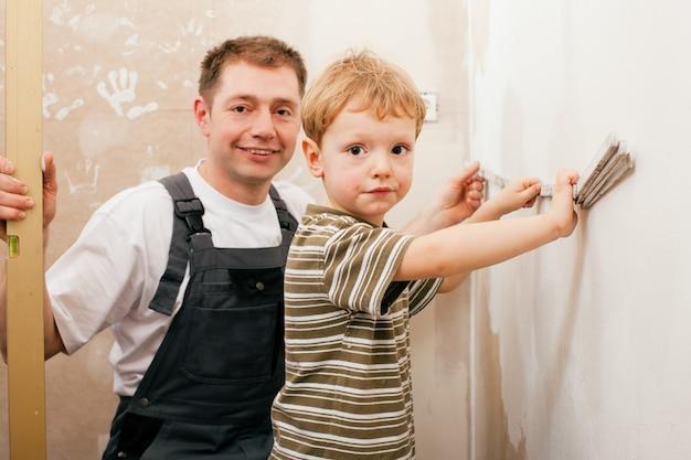 Père et fils mesurant une cloison sèche