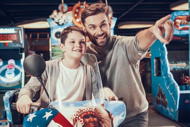 Père et fils sur une moto jouet avec impatience