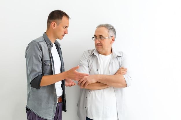 Père et fils mûrs, querelle, isolés sur mur blanc