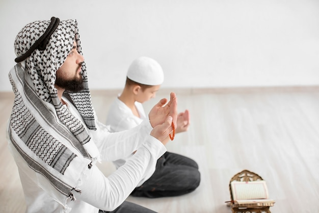 Père et fils musulmans priant ensemble
