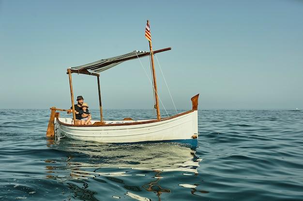 Un père et un fils naviguant dans un bateau vintage classique