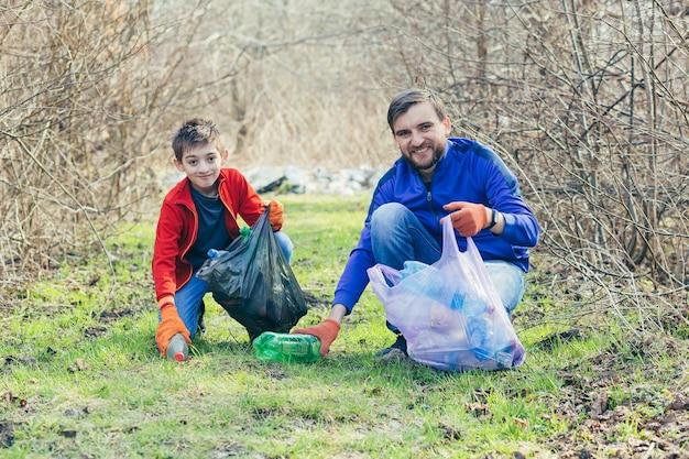 Père et fils nettoient le parc des déchets, les bénévoles nettoient la forêt des bouteilles en plastique et passent du temps ensemble