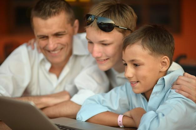 Père et fils avec ordinateur portable à la table