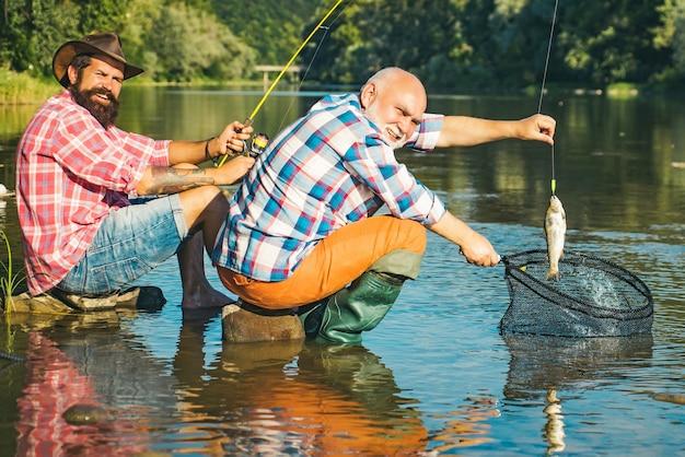Père avec fils sur la pêche en rivière. pêcheur à la mouche sur la rivière. pêche à la truite d'eau calme