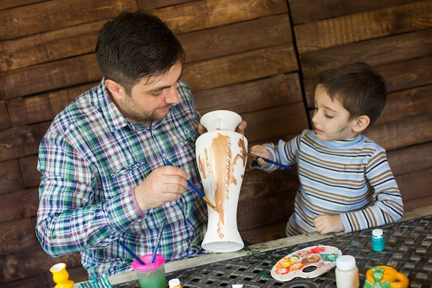 Père et fils peignent un vase