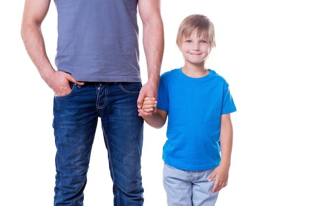 Père et fils. père et fils se tenant la main en se tenant isolé sur blanc