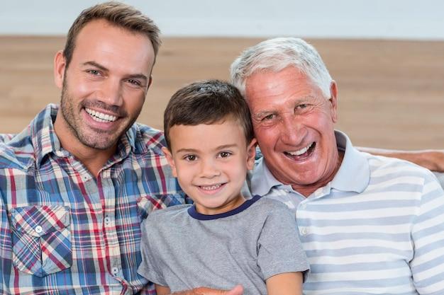 Père, fils et petit-fils assis sur un canapé