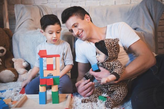Père, fils et petite fille jouent.