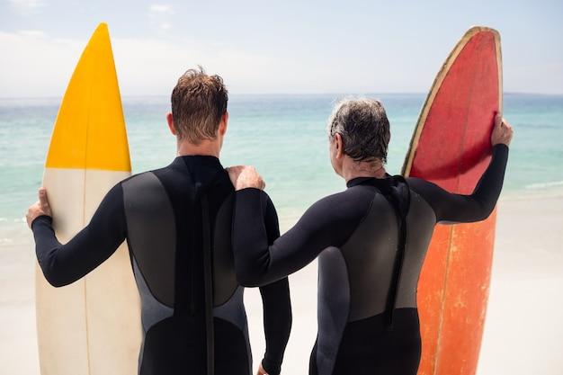 Père et fils avec planche de surf debout sur la plage